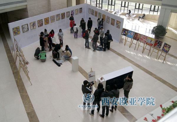 12月21日上午,西安欧亚学院艺术设计学院《BE HAPPY》画展在图书馆大厅正式开幕,这些作品是09级视觉传达专业的学生在国际新媒体工作室负责人王谦老师指导下完成的。展厅中间是学生利用废旧衣服通过自己的想法和创意现场制作的一些装置,整个展览的海报也是学生全手工制作完成。    西安欧亚学院艺术设计学院副院长于海、艺术设计学院院长助理曹锋、国际新媒体班外教Juliette参加了本次画展开幕式,并邀请了副院长田焱、西安法语联盟法方校长Thierry COSTE 前来观看。田副院长看完作品后给予了高度评价